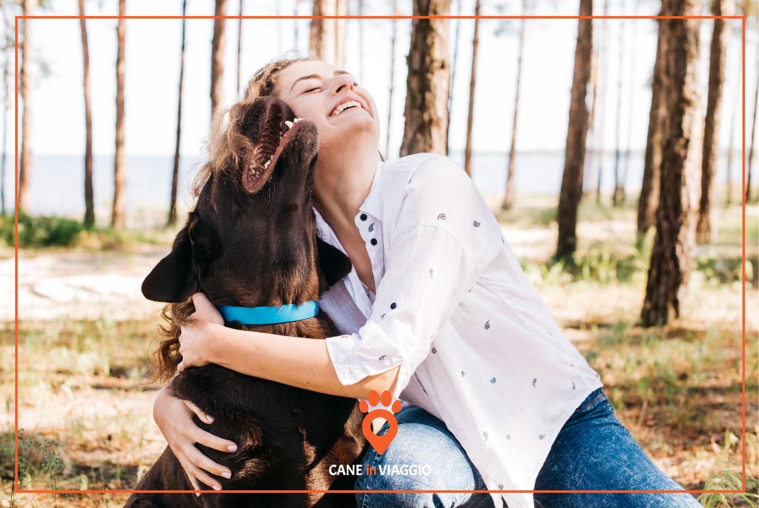 padrona e il suo cane si abbracciano in un bosco